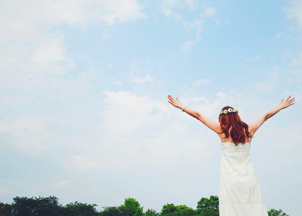 青空の下で手を広げる女の子