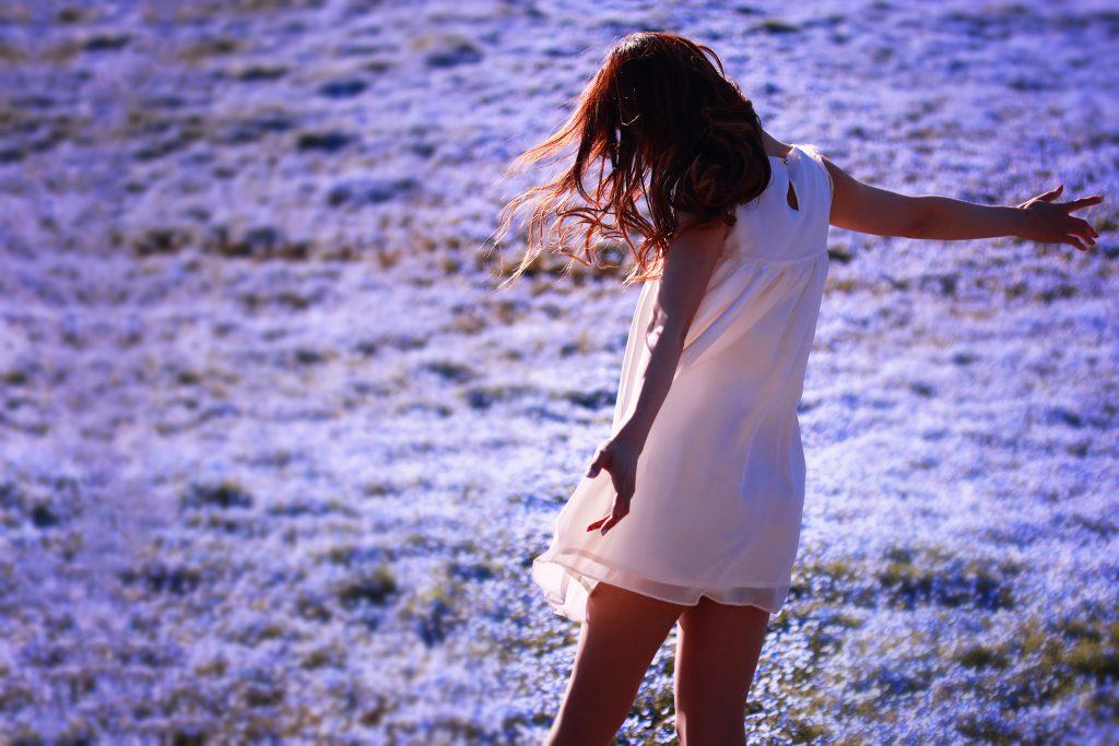 ネモフィラの花畑で全身に春の風を浴びている女の子の写真画像