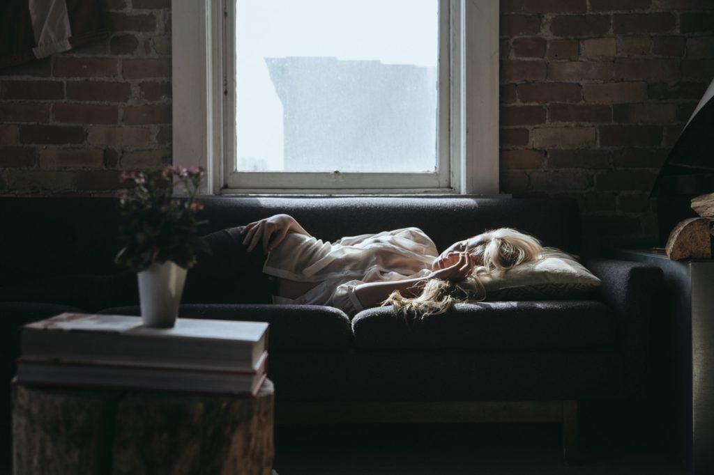 頭痛で寝込む女性