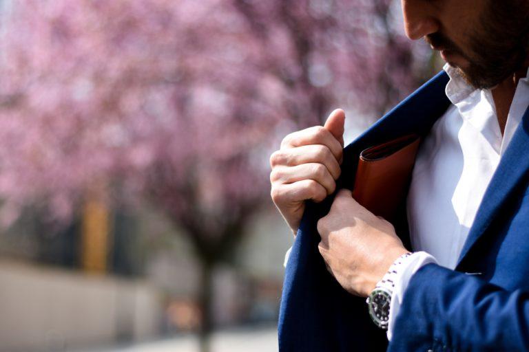 胸ポケットへ財布をしまうダンディな男性
