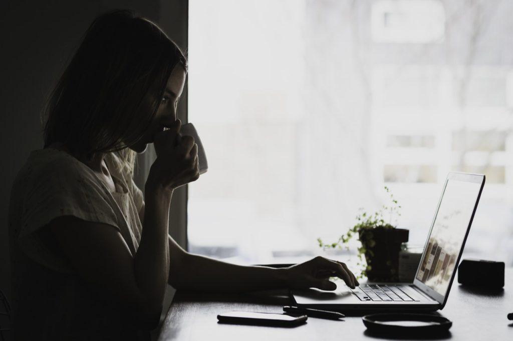 コーヒーを飲みながらパソコンを操作する女性