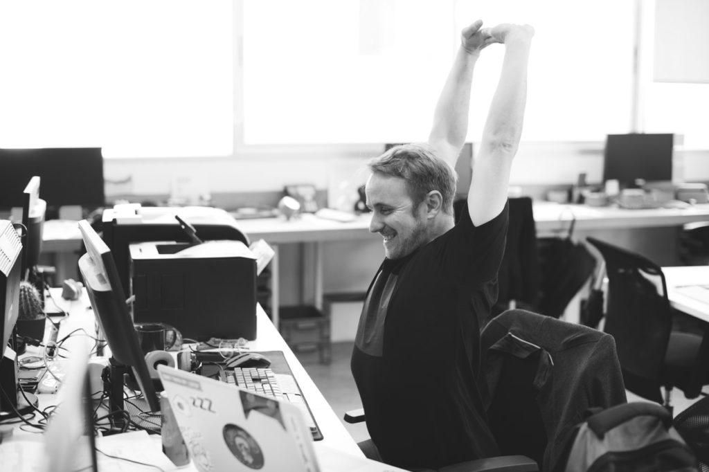仕事中に伸びをしている男性