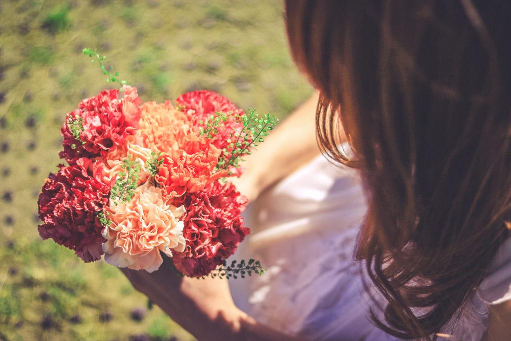 公園でしゃがんで花を見つける女の子